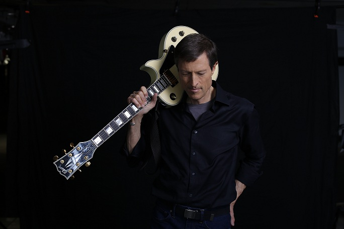 Neal with guitar on shoulder re_b